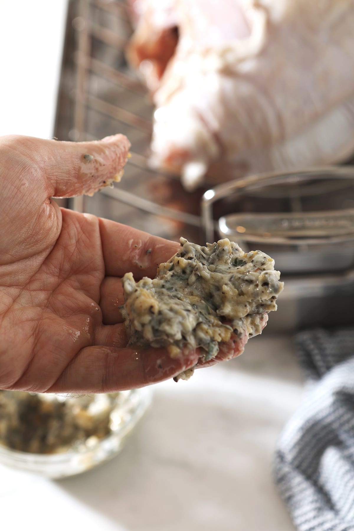 A hand holds homemade herb butter in front of a raw turkey breast