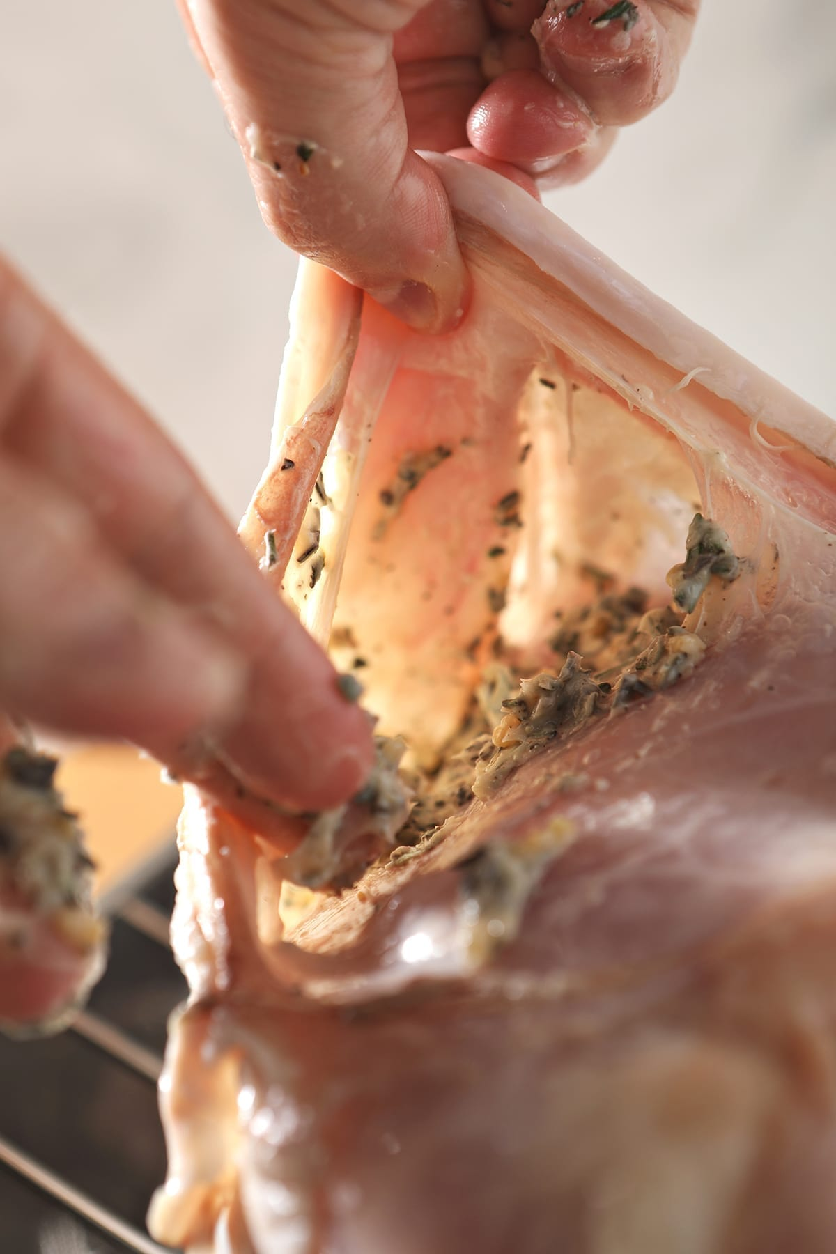 Two hands hold up and rub herb butter beneath the skin of a turkey breast