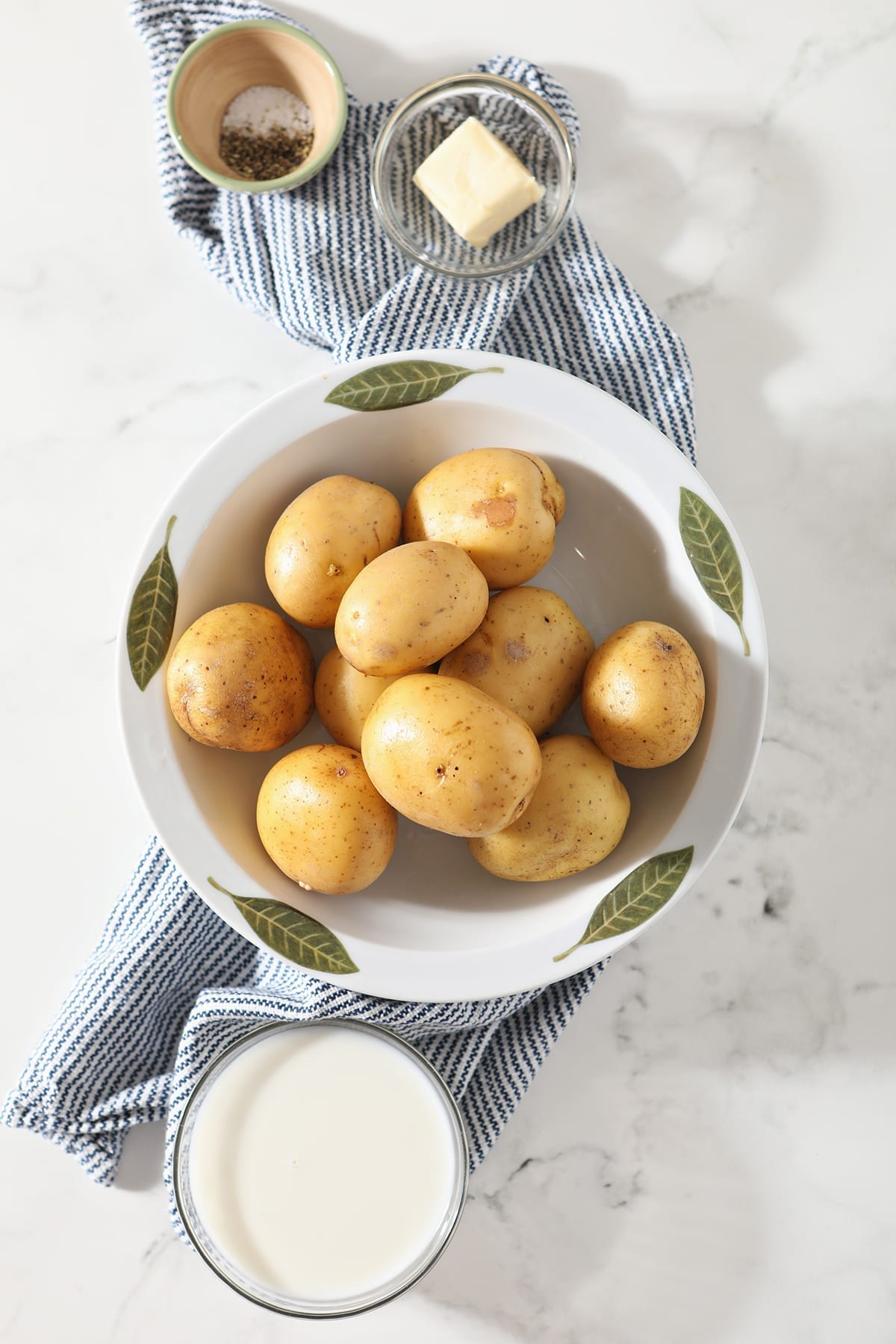 Gold potatoes sit in a decorative bowl on top of a blue and white striped towel next to a bowl of milk, butter and seasonings