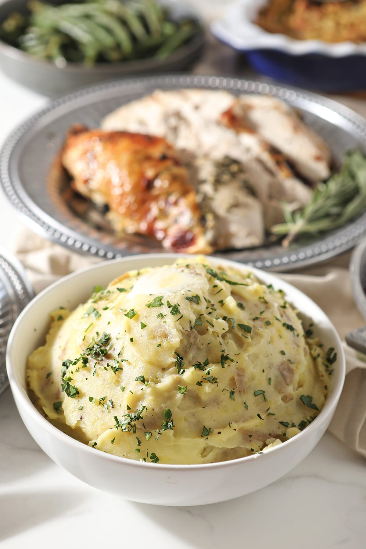 A bowl of mashed potatoes sits in front of a silver platter holding turkey, surrounded by other holiday dishes