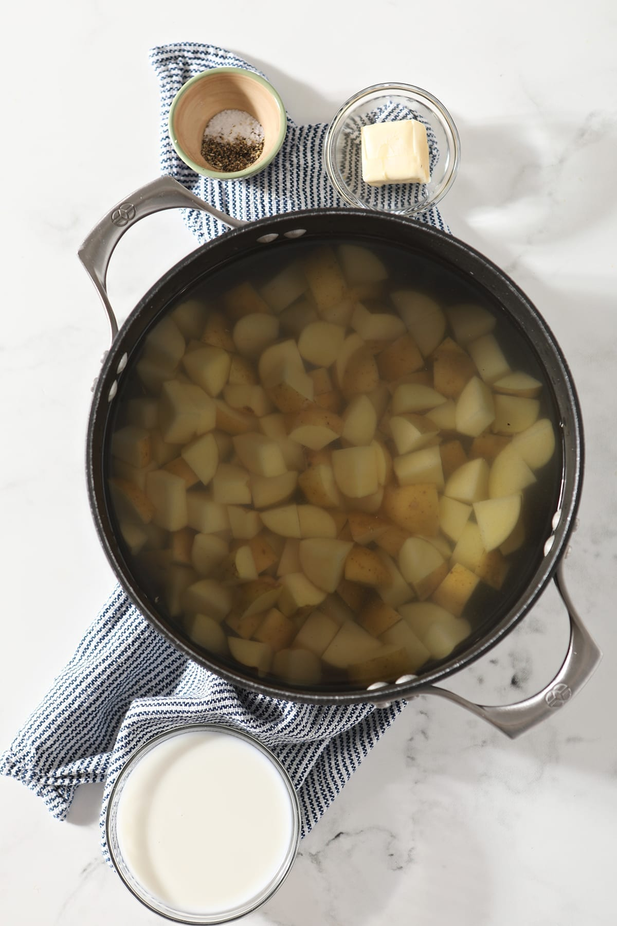 A large pot holding chopped potatoes sits next to other mashed potato ingredients while sitting on top of a blue and white striped towel