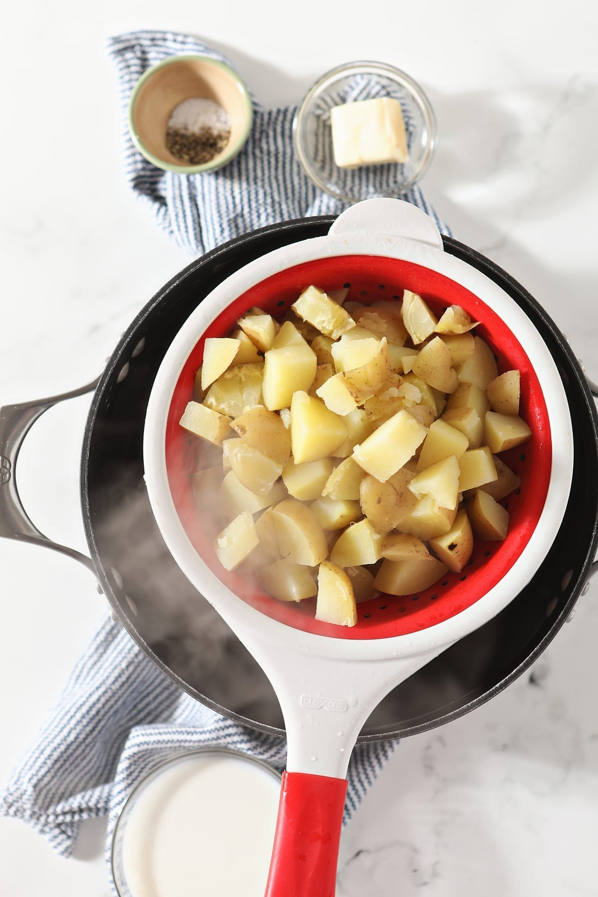 Steam streams off recently boiled potatoes in a red and white colander