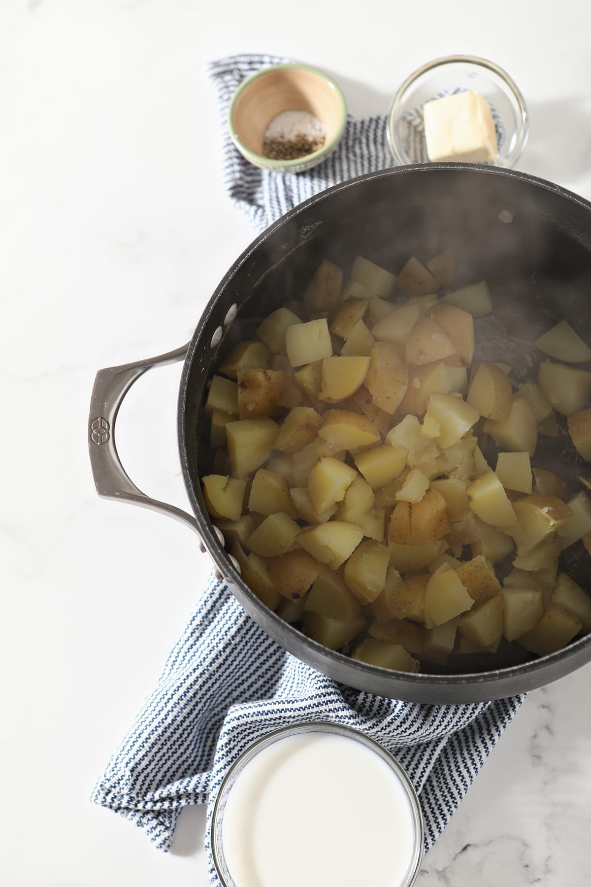 Boiled potatoes sit in a black pot next to bowls of milk, butter and seasonings
