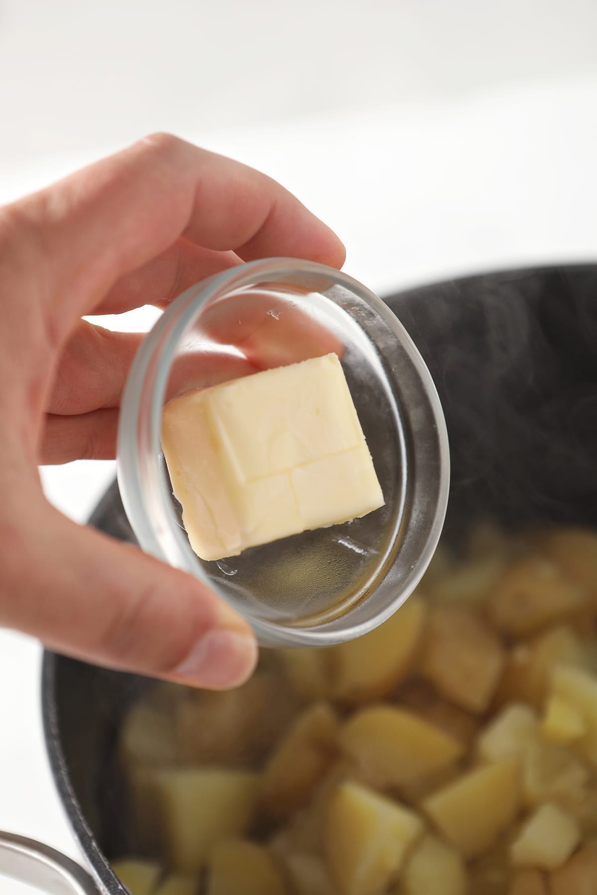 A bowl of softened butter is held over a pot holding boiled potatoes