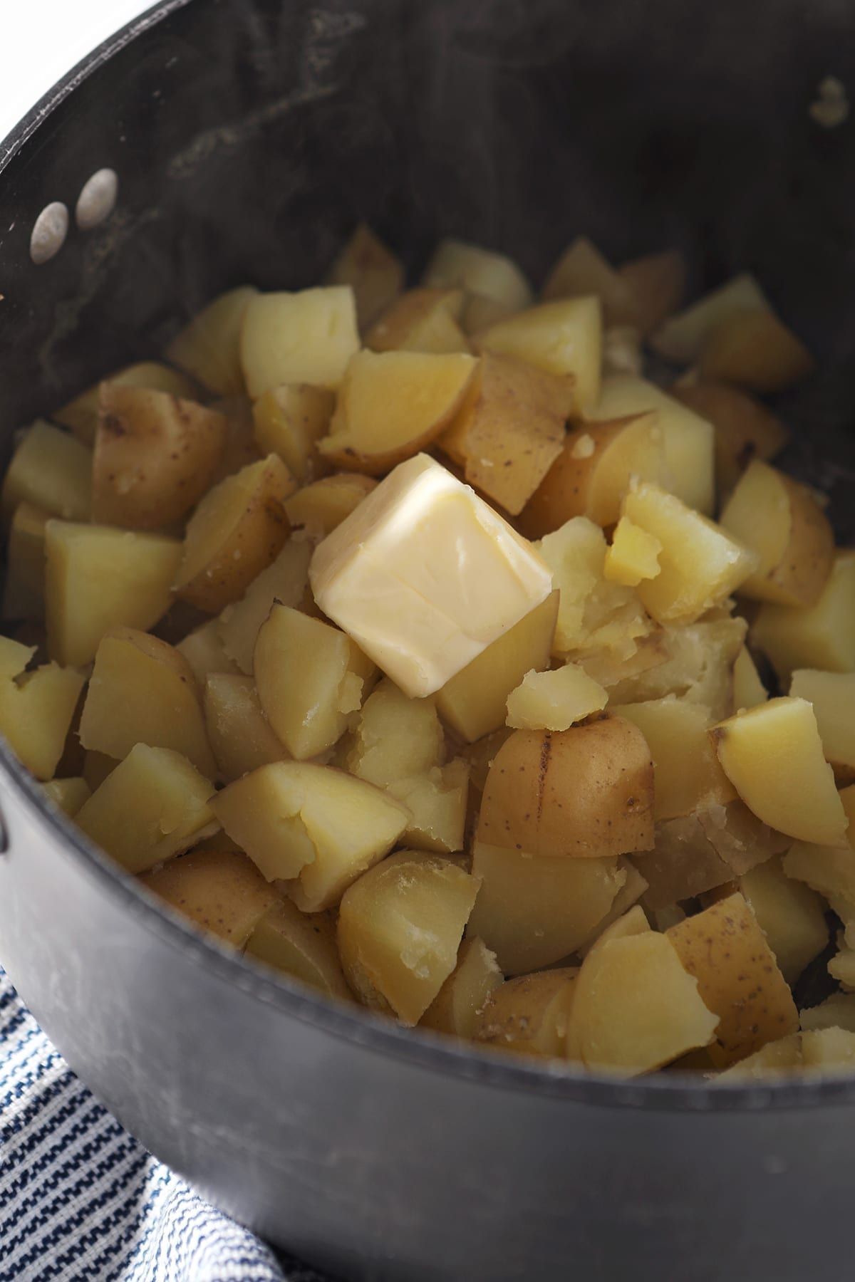 Butter sits on top of boiled potatoes