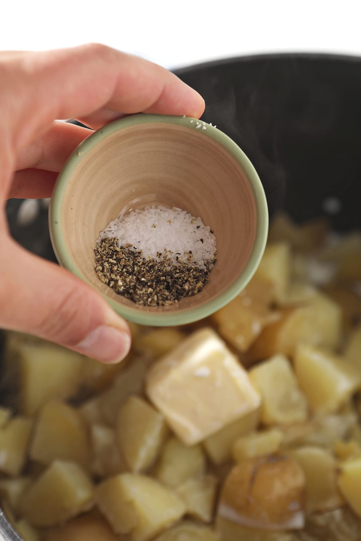 Salt and pepper are sprinkled from a bowl into a pot holding potatoes and other ingredients