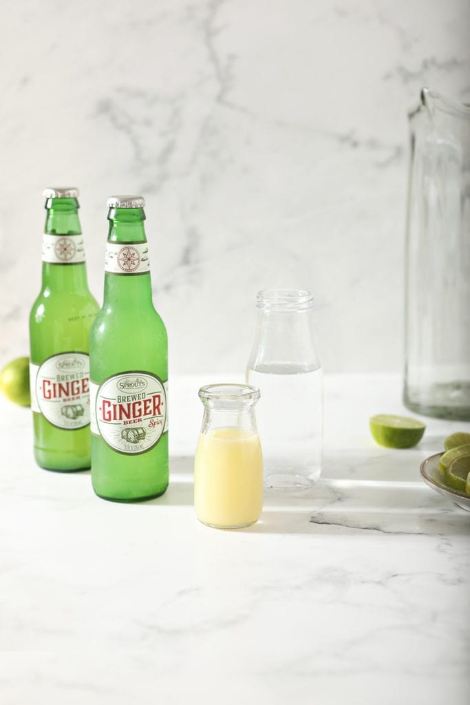 A bottle of lime juice with a bottle of vodka and two bottles of ginger beer on marble next to an empty pitcher and halved limes