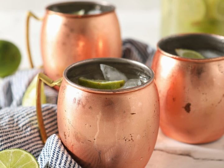 Three copper mugs sitting on a blue and white striped towel hold Moscow mules garnished with lime wedges on marble with a pitcher behind them
