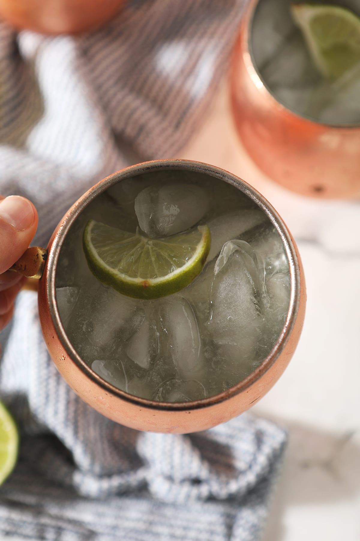 Close up of a Moscow mule inside a copper mug behind held above a blue striped towel