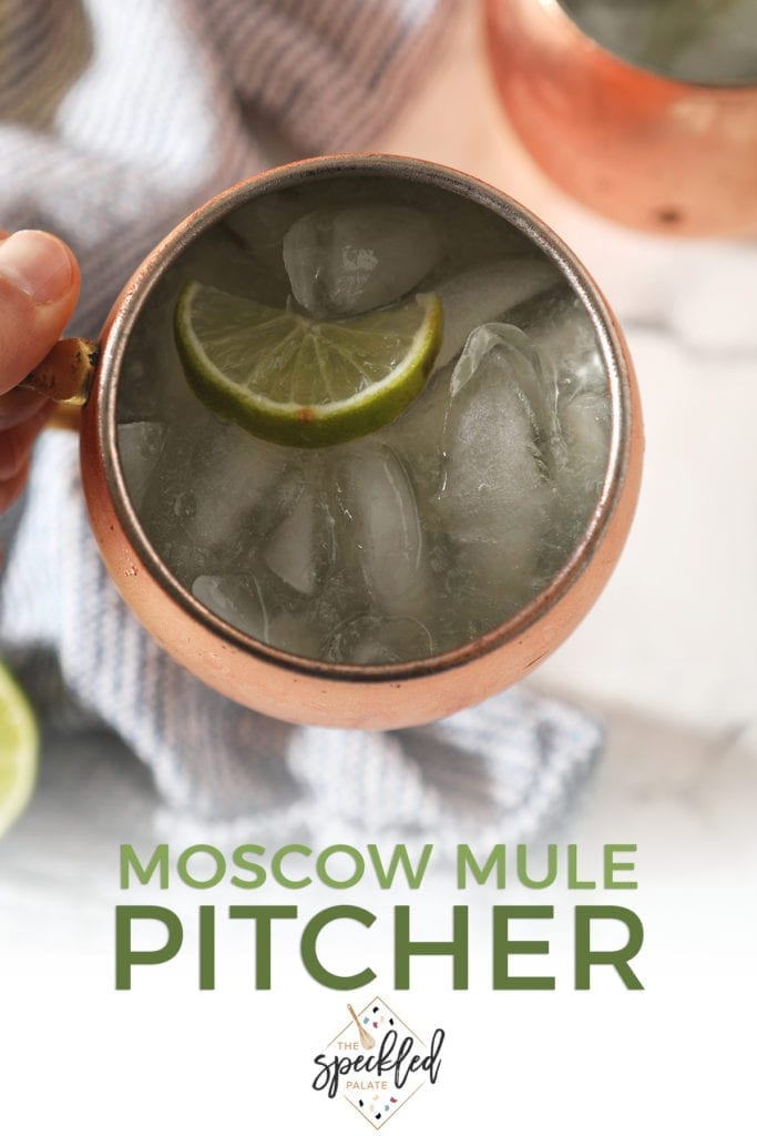 Close up of a Moscow mule inside a copper mug behind held above a blue striped towel with the text 'moscow mule pitcher'