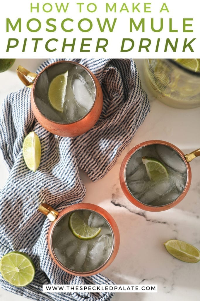 Three Moscow Mules garnished with lime wedges in copper mugs sit on a blue and white striped towel with a pitcher sitting nearby with the text 'how to make a moscow mule pitcher drink'