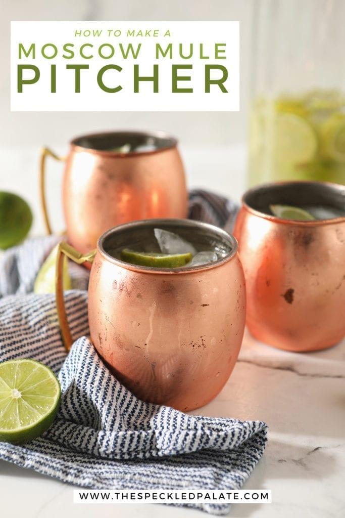 Three copper mugs sitting on a blue and white striped towel hold Moscow mules garnished with lime wedges on marble with a pitcher behind them with the text 'how to make a moscow mule pitcher'