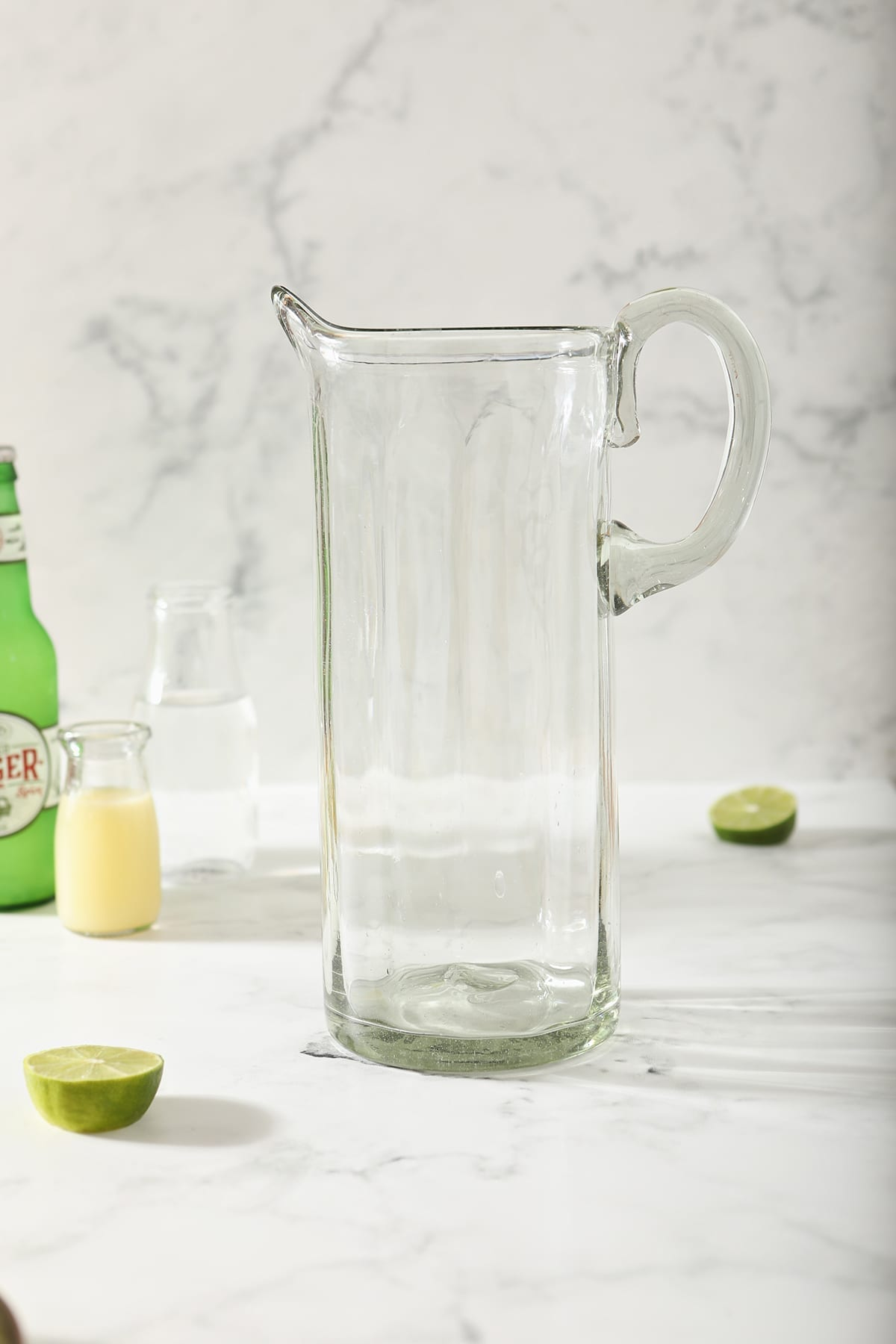 An empty pitcher next to lime juice, vodka and ginger beer