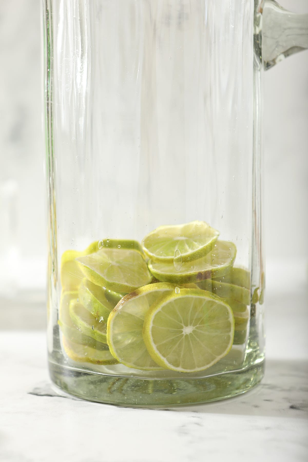 Close up of lime rounds in a tall pitcher sitting on marble