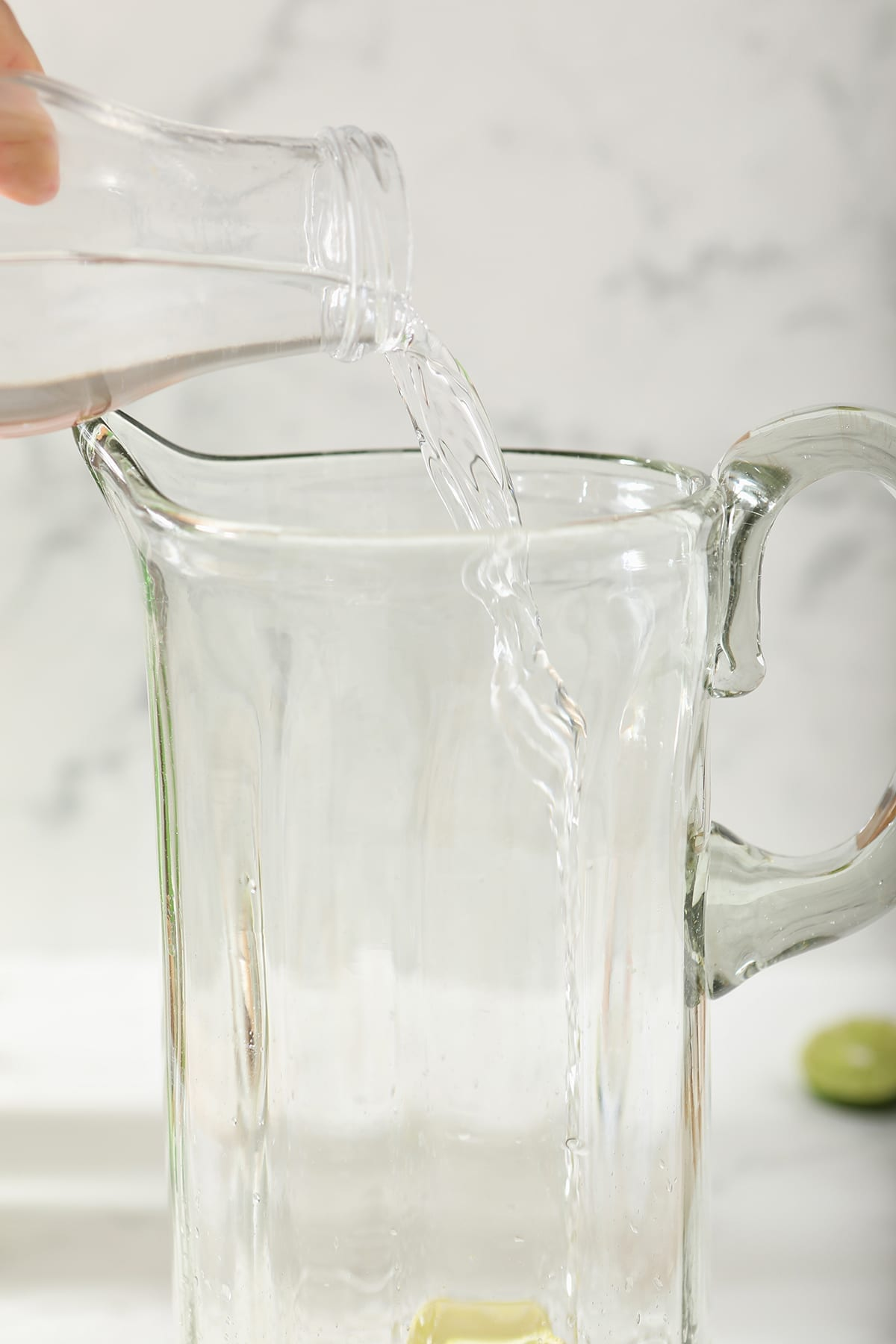 Vodka pours into a tall pitcher
