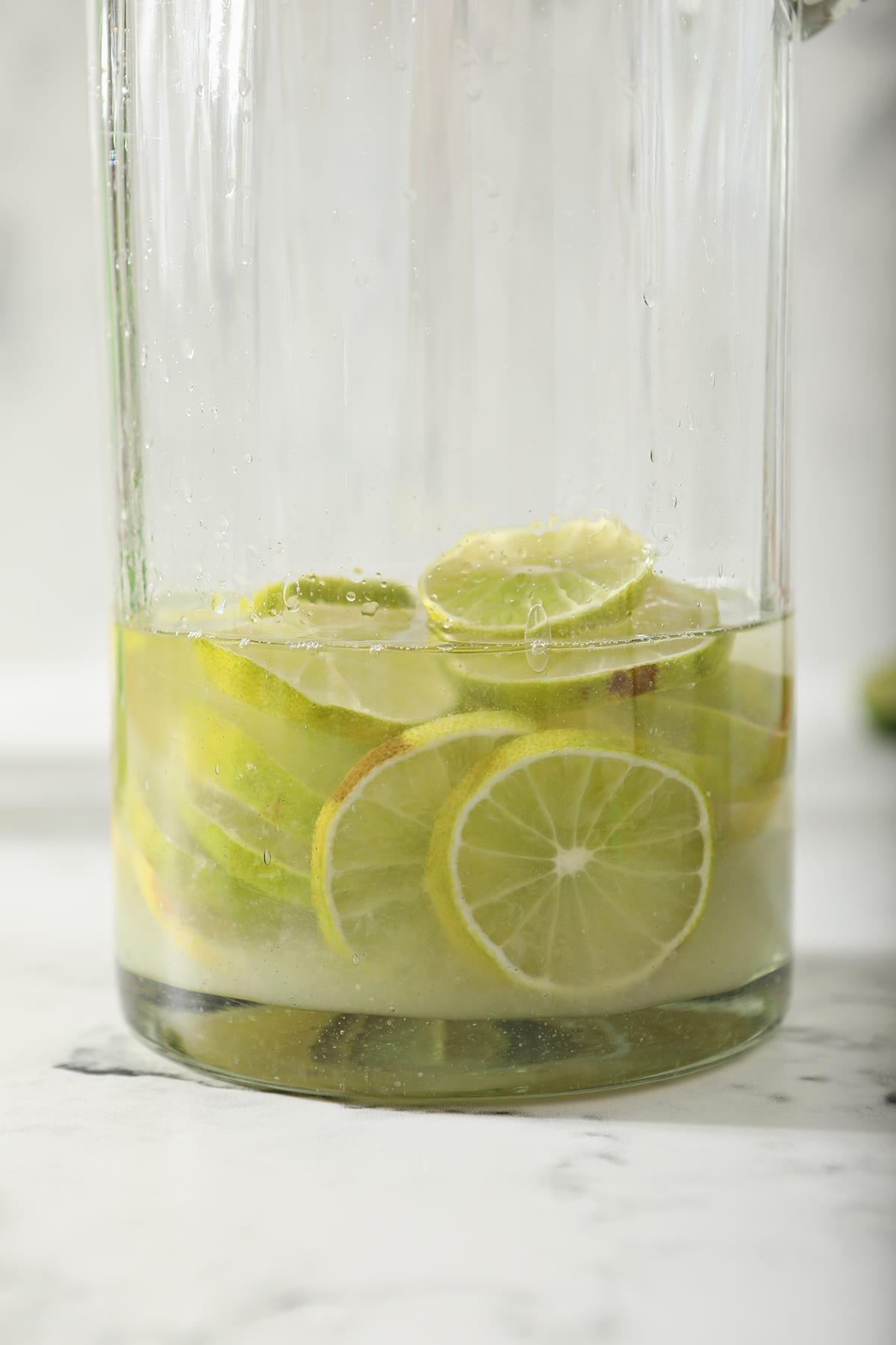 Liquid on top of lime rounds in a tall pitcher