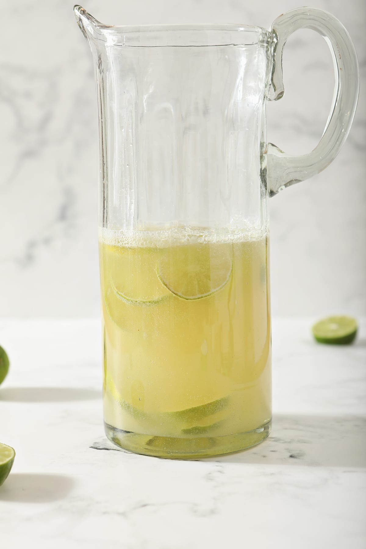 A Moscow Mule Pitcher with lime rounds inside the pitcher on marble