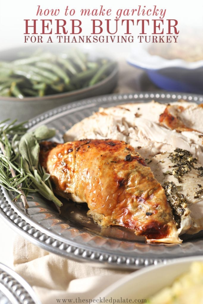Roasted turkey breast on a silver platter next to fresh herbs with the text 'how to make garlicky herb butter for a thanksgiving turkey'