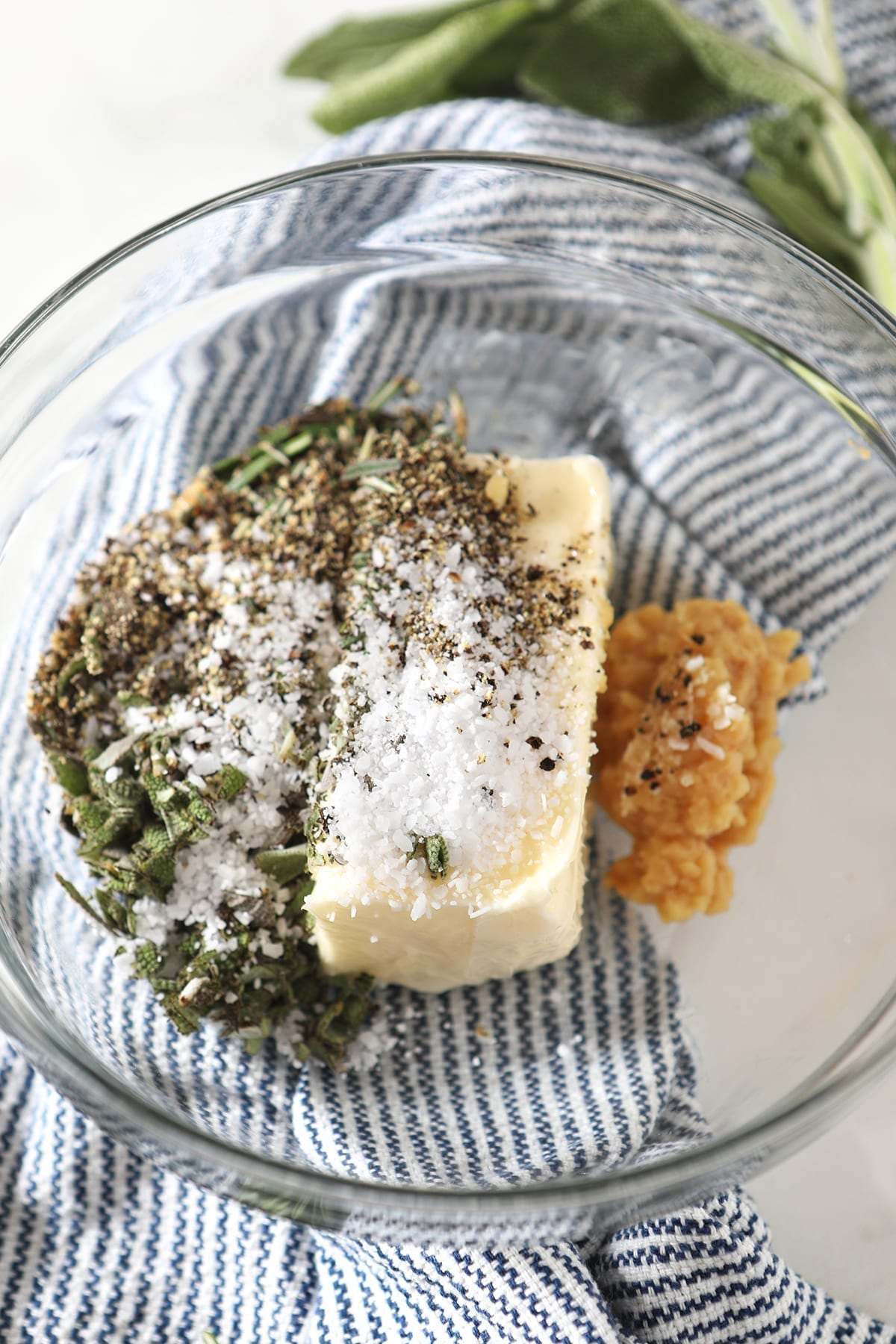 Herb butter ingredients in a glass bowl sitting on a blue striped towel before blending