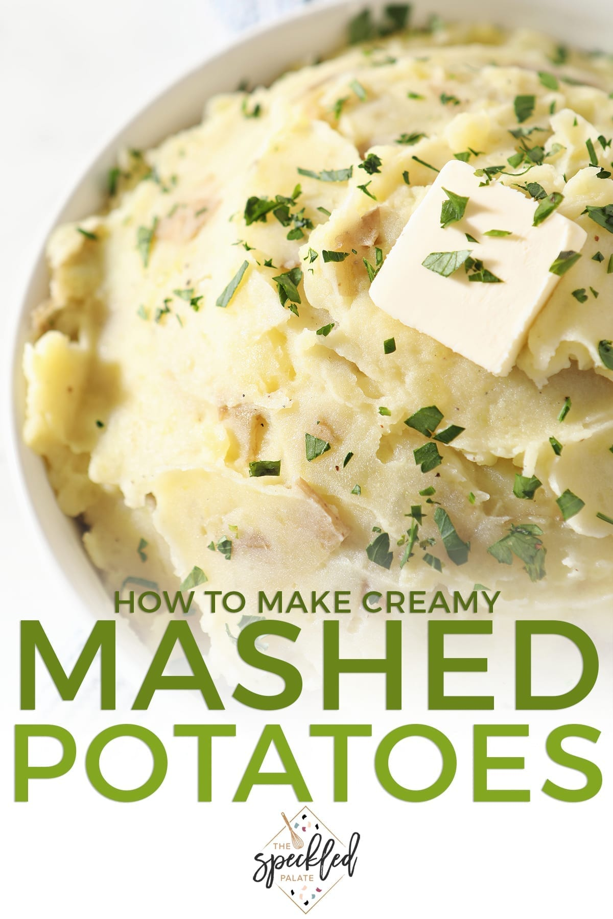 Close up of a white bowl holding mashed potatoes with a butter pat on top with the text 'how to make creamy mashed potatoes'