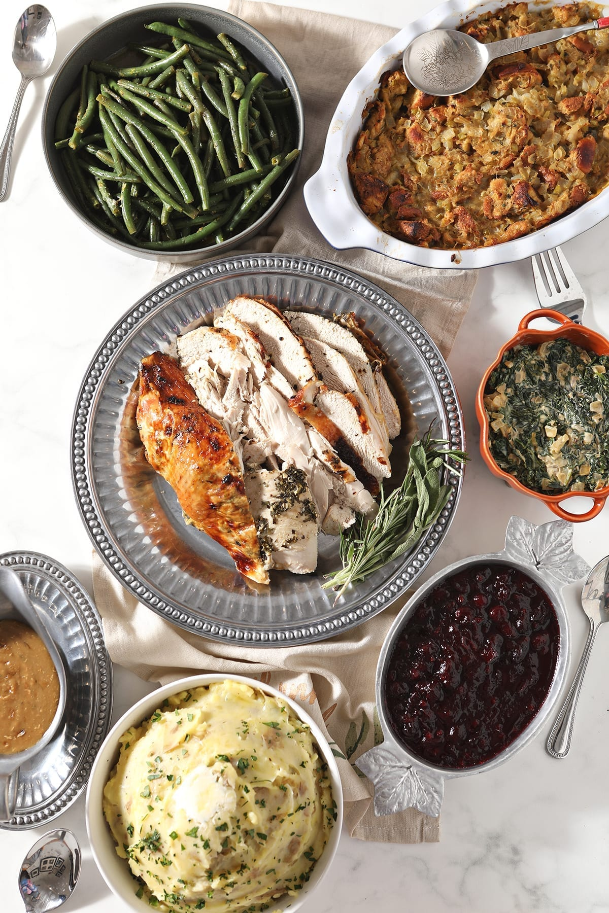 Roasted Herb Butter Turkey Breast surrounded by holiday side dishes on a marble table