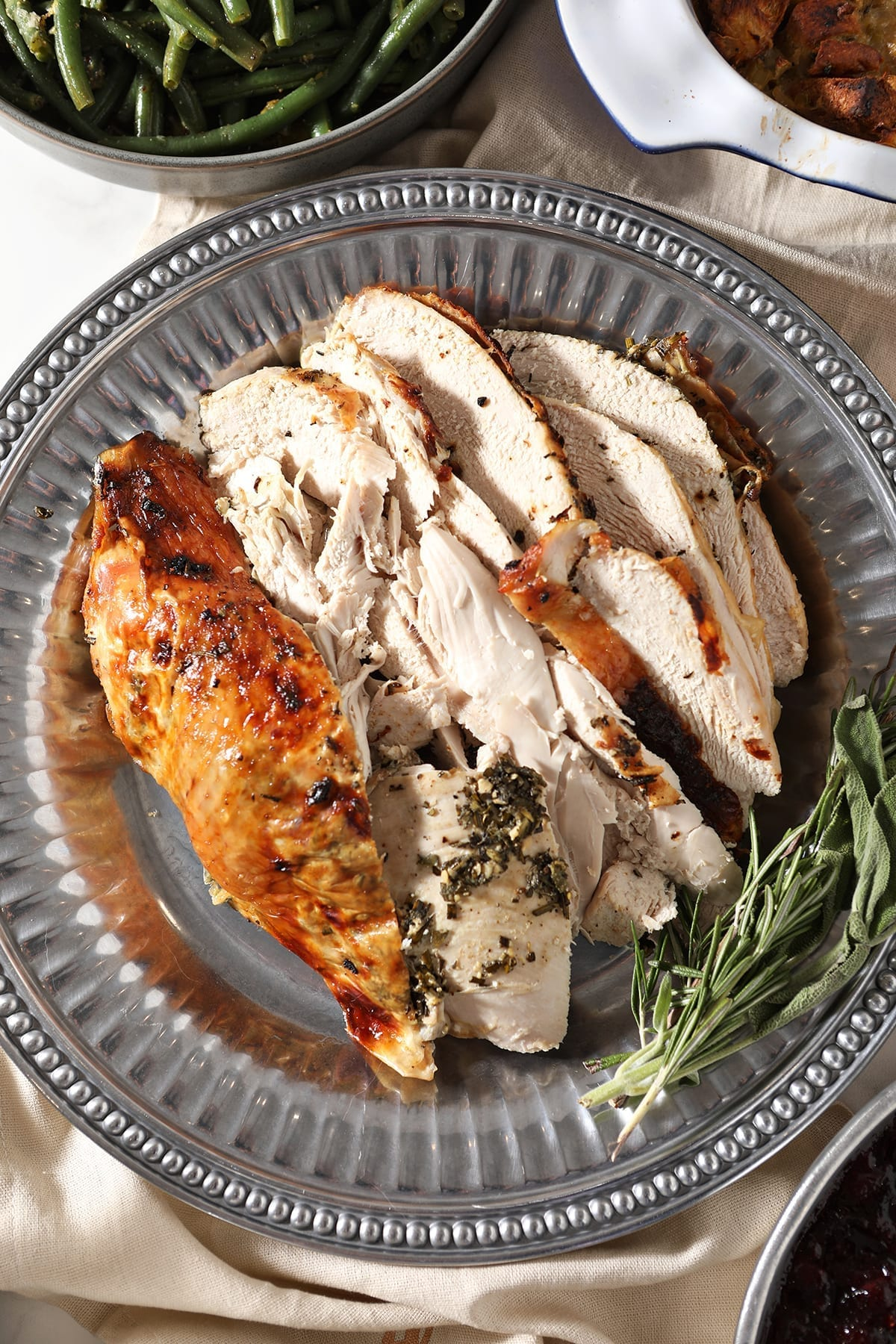 Close up of roasted turkey breast with herb butter on a silver platter