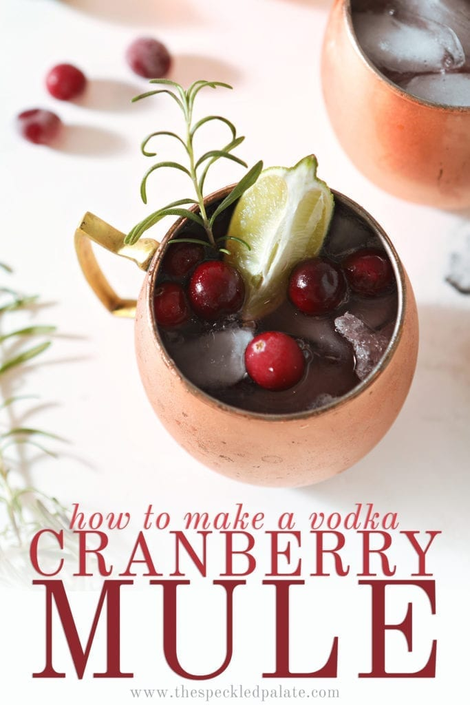 A Cranberry Moscow Mule from above garnished with a lime, cranberries and a rosemary sprig next to two other copper mule mugs with the text 'how to make a vodka cranberry mule'