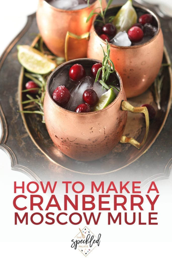 Three Yule Mules, garnished with fresh cranberries, lime wedges and rosemary sprigs, sit on a silver platter with the text 'how to make a cranberry moscow mule'