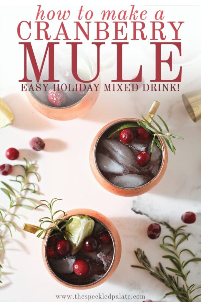 Three Cranberry Mules sit on a marble surface next to a bowl of cranberries, a gold jigger, rosemary sprigs and more cranberries with the text 'how to make a cranberry mule. easy holiday mixed drink!'