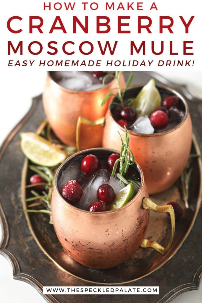 Three Yule Mules, garnished with fresh cranberries, lime wedges and rosemary sprigs, sit on a silver platter with the text 'how to make a cranberry moscow mule. easy homemade holiday drink!'