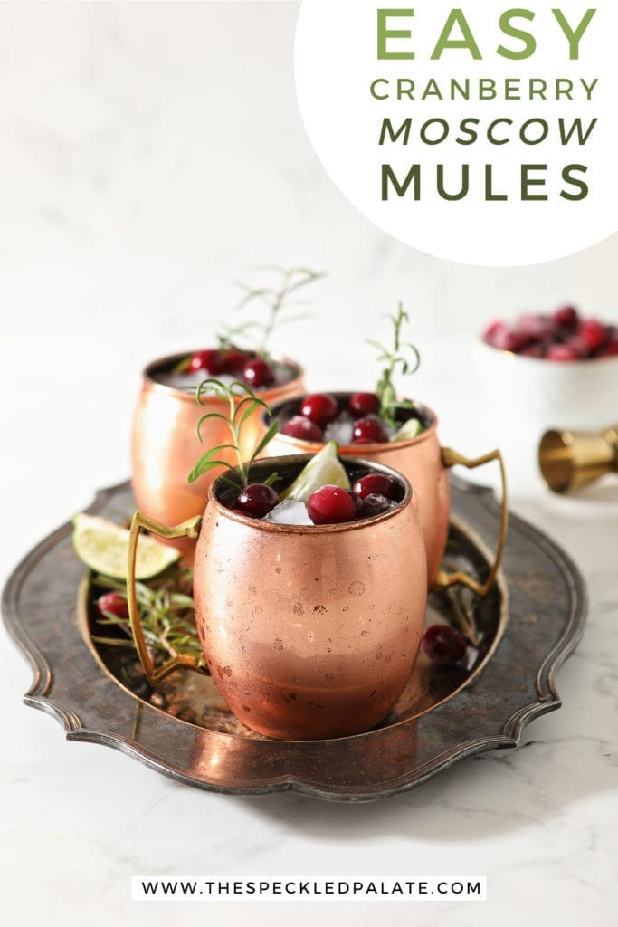 Three Yule Mules, garnished with fresh cranberries, lime wedges and rosemary sprigs, sit on a silver platter with the text 'easy cranberry moscow mules'