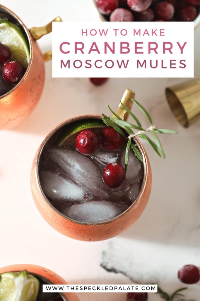 Close up of a copper mug holding a yule mule, garnished with a slice of lime, cranberries and a rosemary twig, with the text 'how to make cranberry moscow mules'