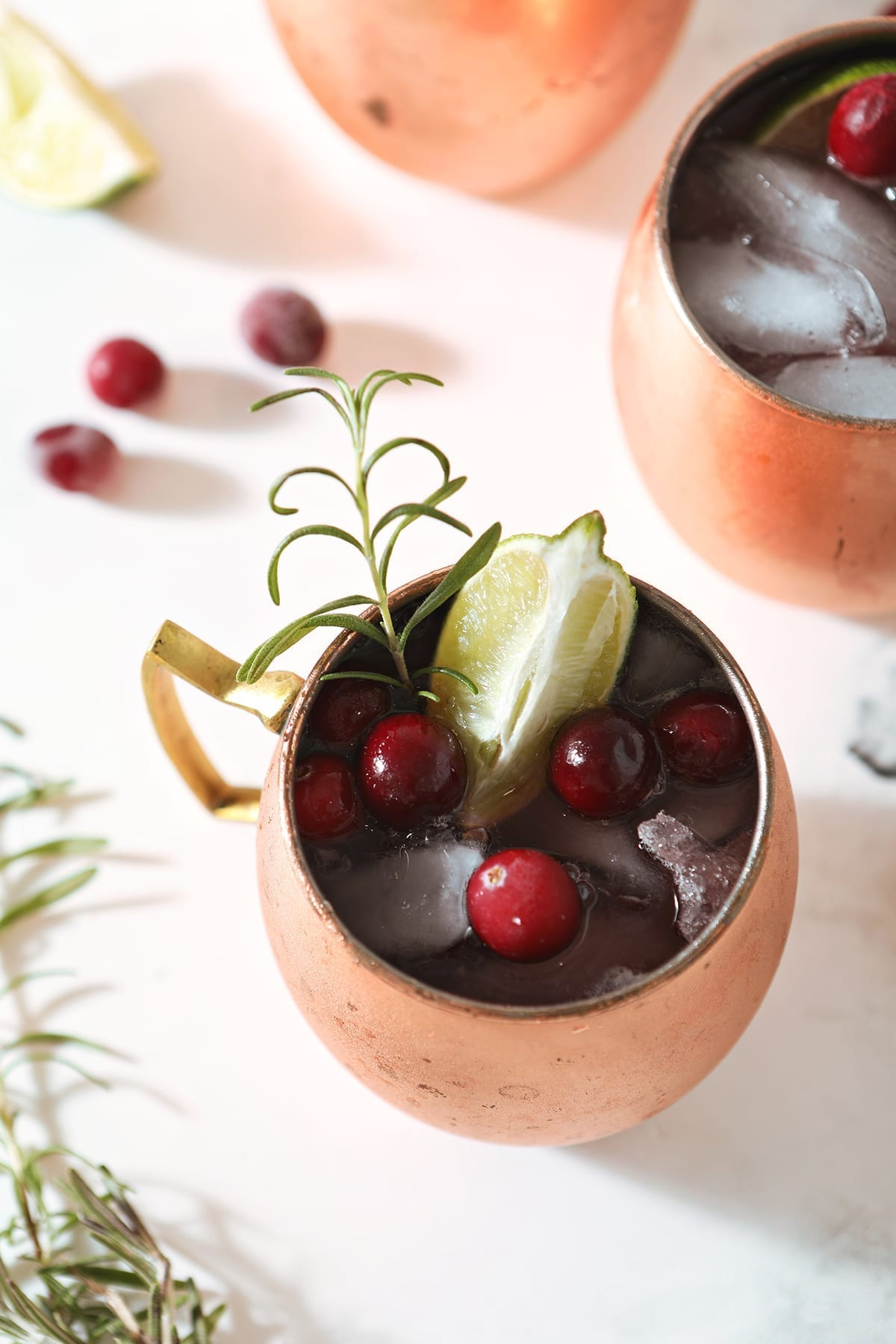 A Cranberry Moscow Mule from above garnished with a lime, cranberries and a rosemary sprig next to two other copper mule mugs