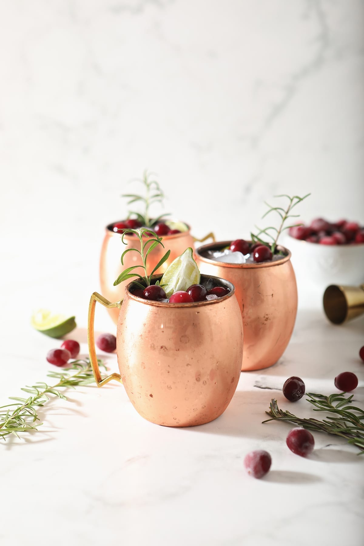 Three Cranberry Moscow Mules in copper cups sit on marble next to sprigs of rosemary and fresh cranberries