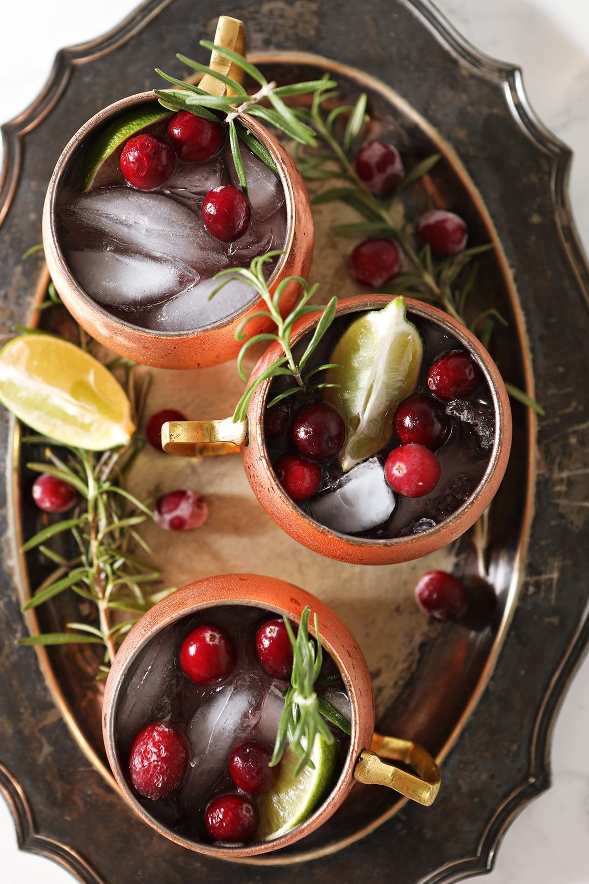 Three Yule Mules, garnished with fresh cranberries, lime wedges and rosemary sprigs, sit on a silver platter