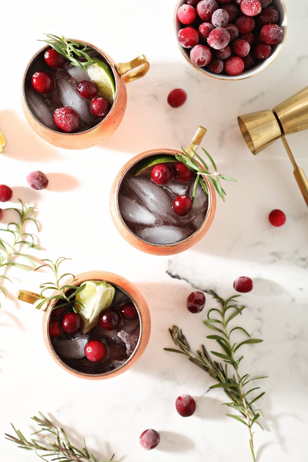 Three Cranberry Mules sit on a marble surface next to a bowl of cranberries, a gold jigger, rosemary sprigs and more cranberries