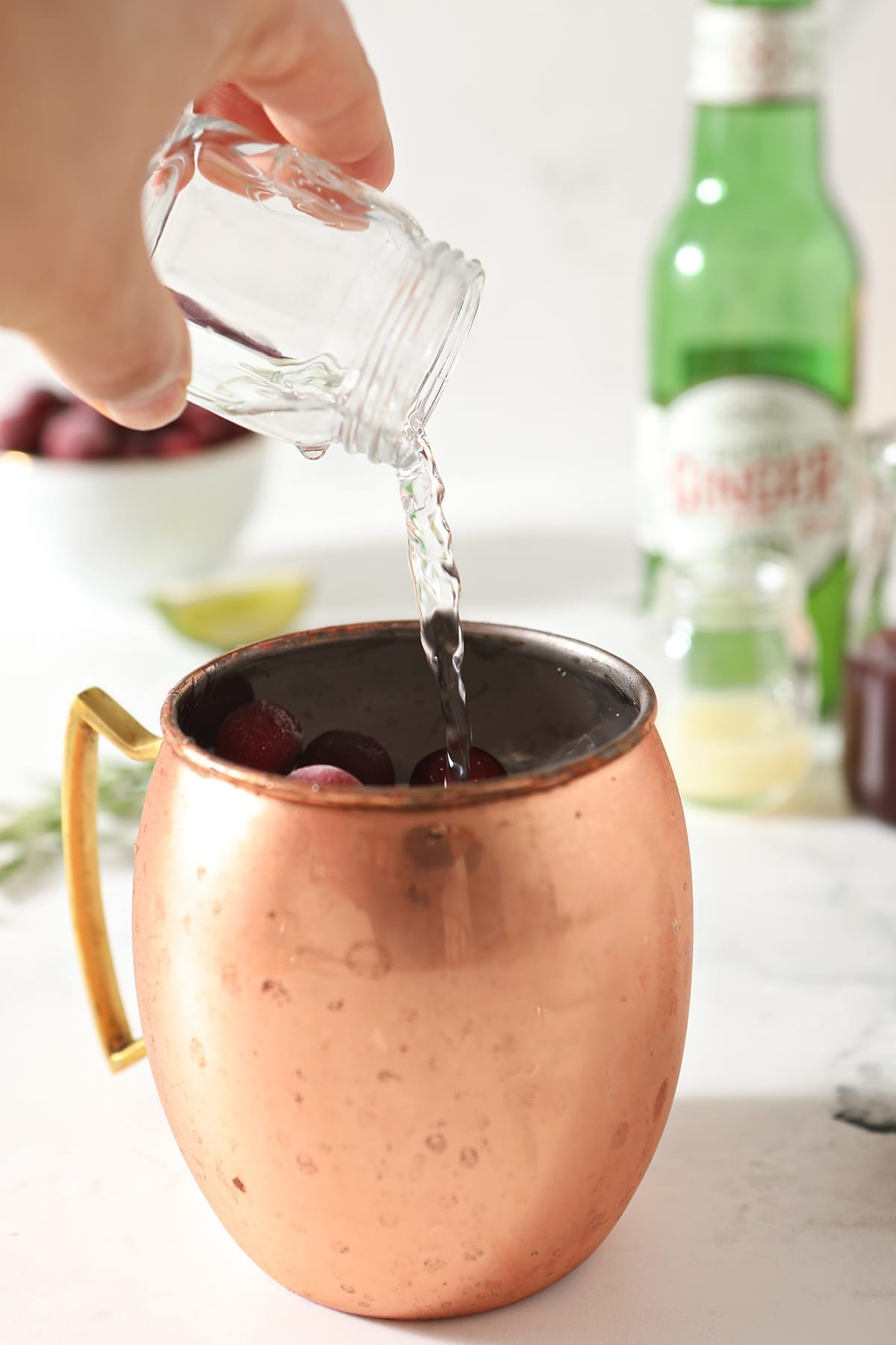 Vodka pours into a copper mug holding ice, syrup and cranberries
