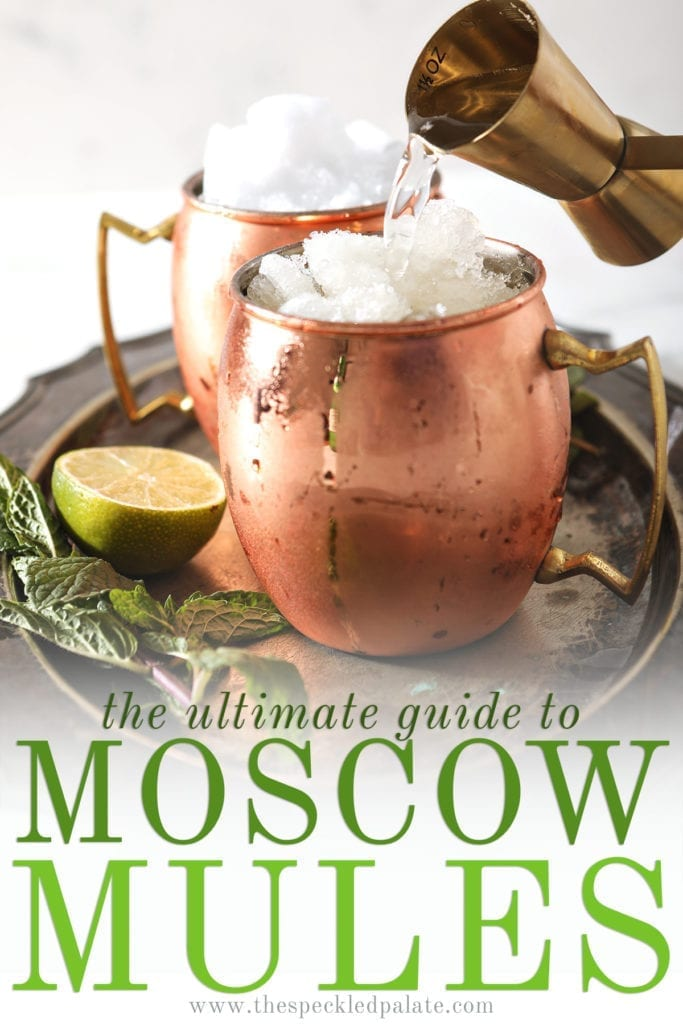 A gold jigger pours liquor into a copper mug filled with snow ice sitting on a silver tray next to mint sprigs and a lime wedge with the text 'the ultimate guide to moscow mules'