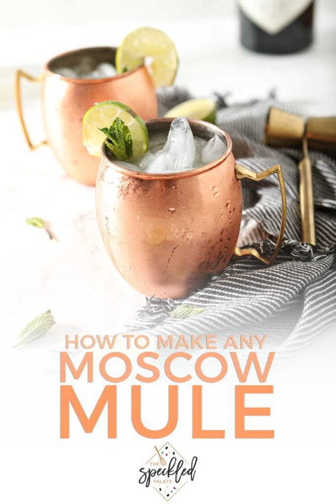 Two Gin Gin Mules in copper mugs sit on top of a gray and white striped towel next to a gold jigger with the text 'how to make any moscow mule'