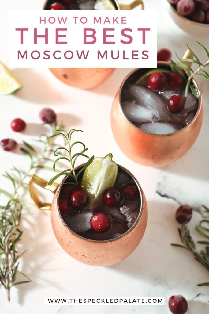 Three Cranberry Mules sit on a marble surface next to a bowl of cranberries, a gold jigger, rosemary sprigs and more cranberries with the text 'how to make the best moscow mules'