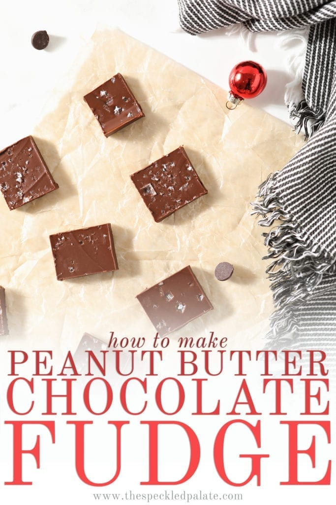 Slices of Peanut Butter Chocolate Fudge on a piece of parchment, surrounded by chocolate chips, festive small ornaments and a gray and white striped towel with the text 'how to make peanut butter chocolate fudge'