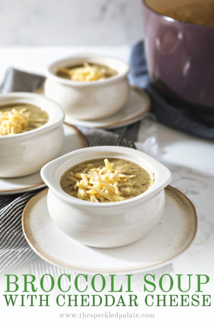 White bowls on pottery plates hold broccoli soup, garnished with extra cheese, on top of gray striped towels and next to a purple Dutch oven with the text 'broccoli soup with cheddar cheese'