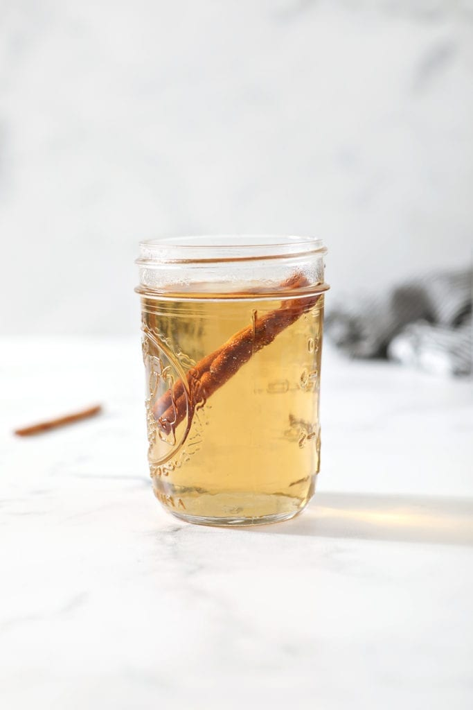 A jar holds simple syrup with cinnamon in it on a marble countertop