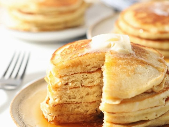 A stack of old fashioned homemade pancakes on a white plate with syrup and butter with a wedge cut out of it