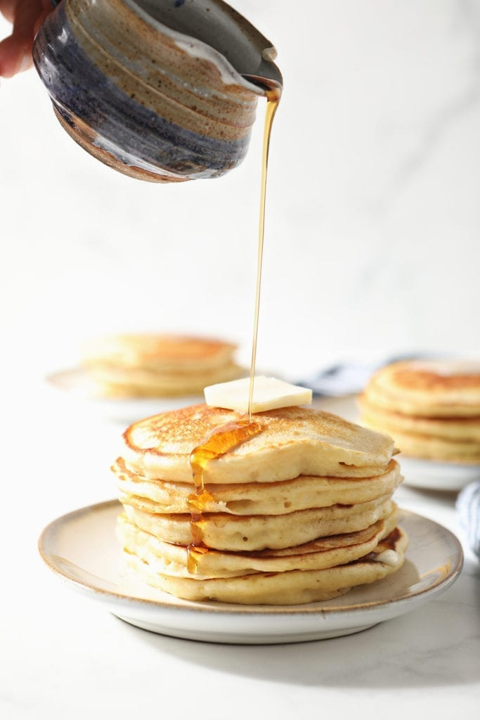 Syrup pours onto a stack of fluffy homemade pancakes