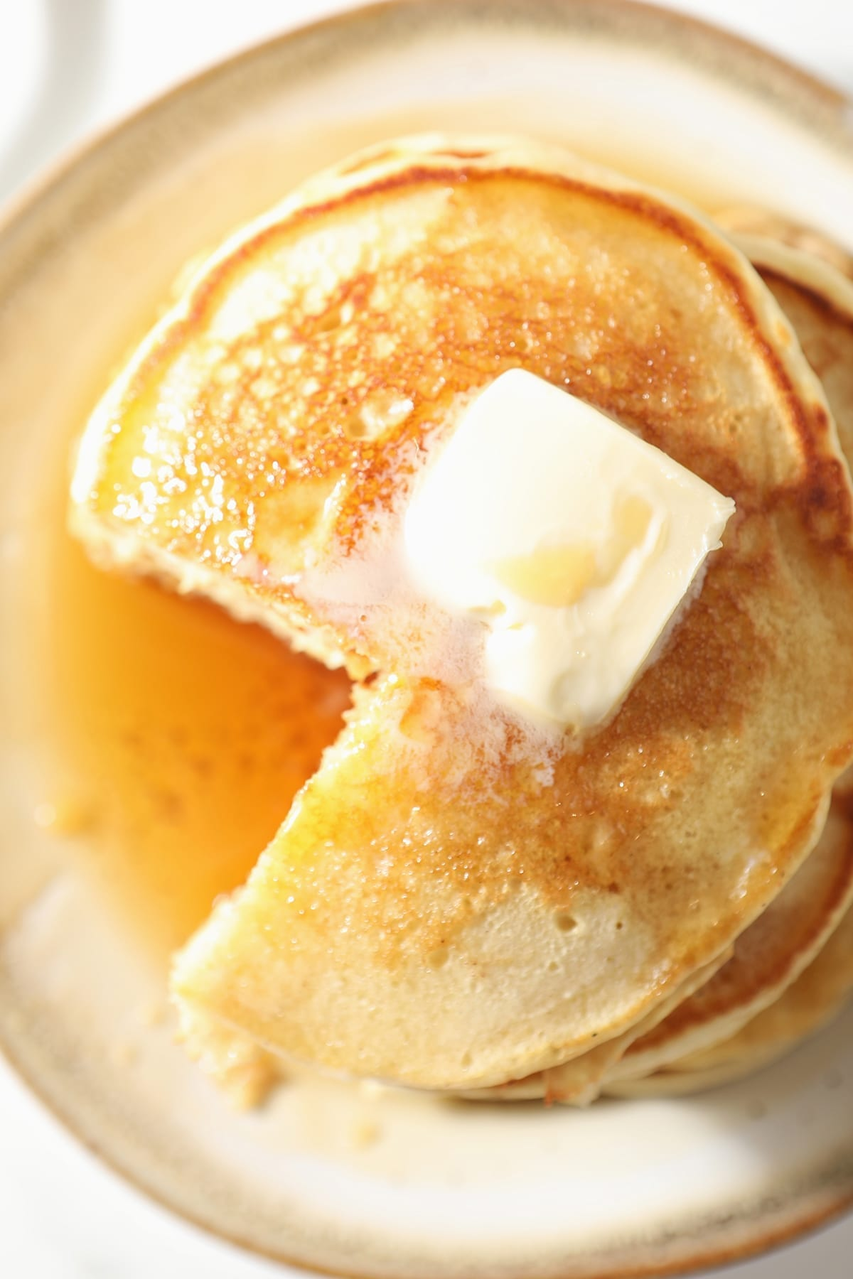 Close up of a stack of pancakes, with a wedge cut out of it, with butter and syrup on top