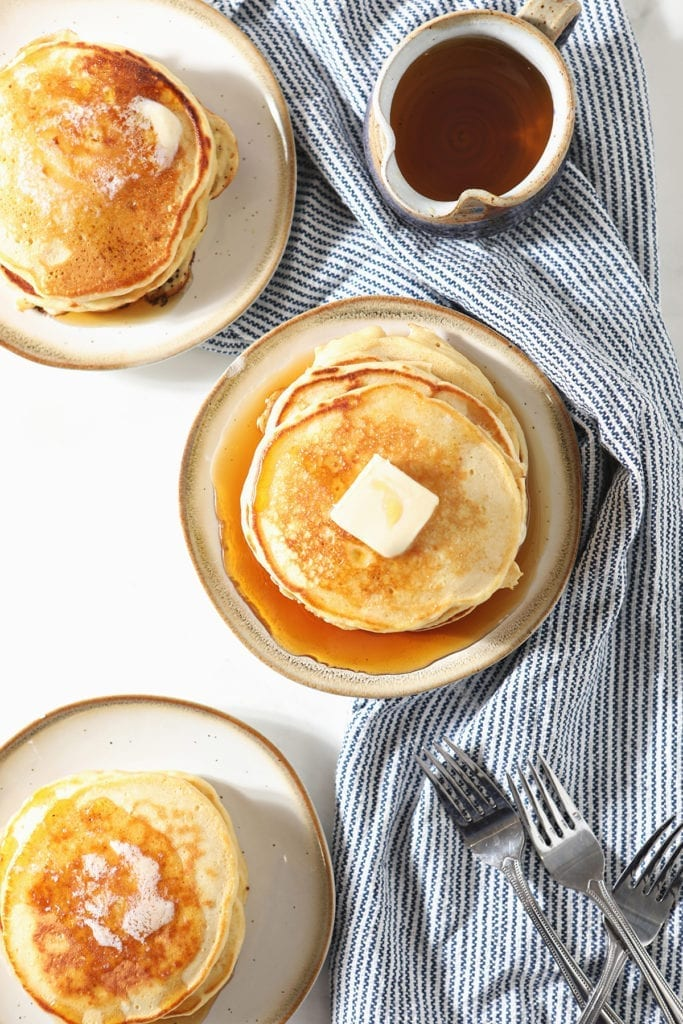 Three plates holding stacks of pancakes topped with butter sit on a blue striped towel next to forks and a container of syrup
