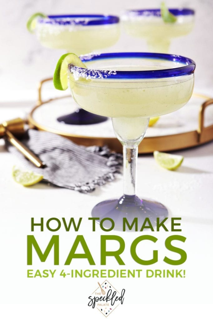 A salt-rimmed margarita sits on marble, in front of a marble tray holding two more with the text 'how to make margs. easy 4-ingredient drink!'