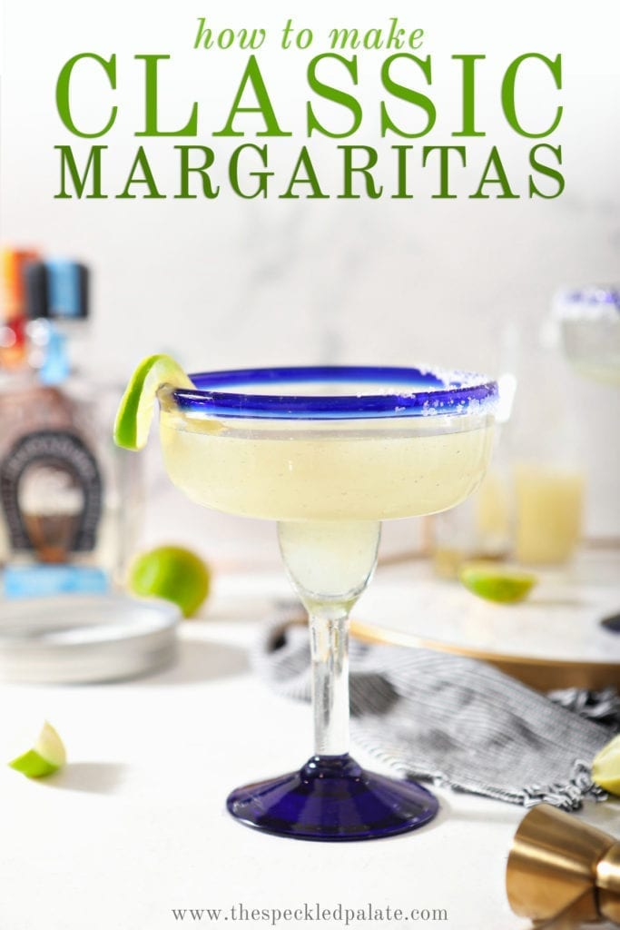 A margarita sits on a marble counter in front of ingredients with the text 'how to make classic margaritas'