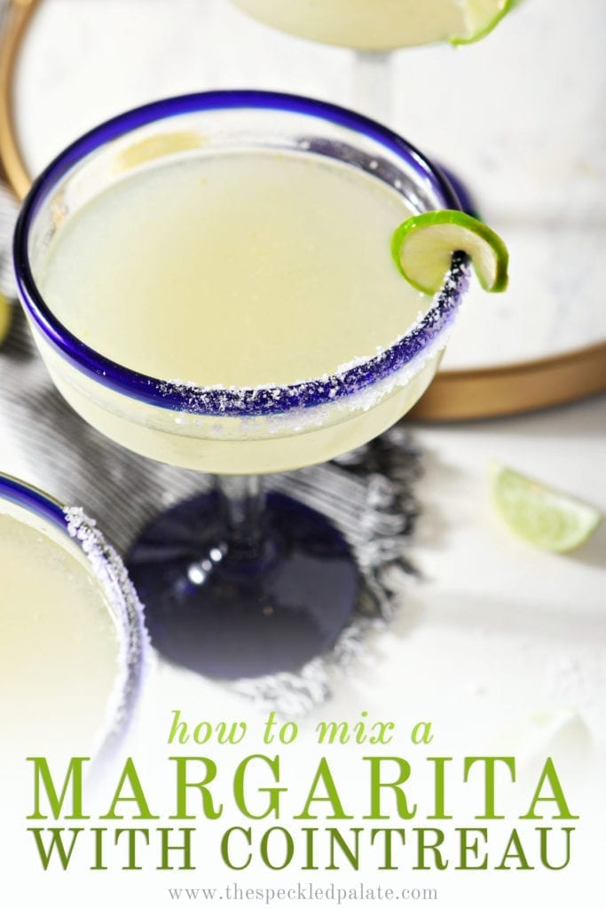 A margarita in blue-rimmed glass sits on a striped towel, surrounded by lime wedges with the text 'how to mix a cointreau margarita'